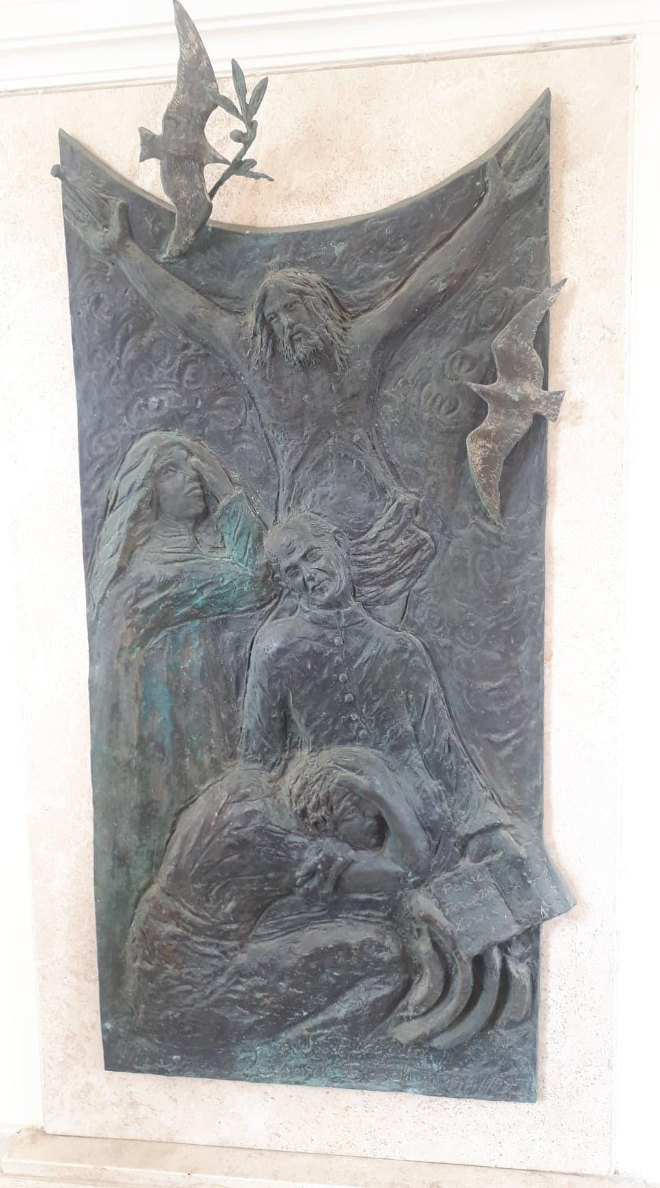 Il bassorilievo in bronzo raffigurante Don Cesare Boschin che alcuni abitanti di Borgo Montello donarono alla parrocchia. Il bassorilievo fu realizzato alla fine degli anni Novanta, tra il '97 e il '98, grazie a una raccolta fondi dei cittadini del Borgo. Il costo del bassorilievo fu di 10 milioni di lire