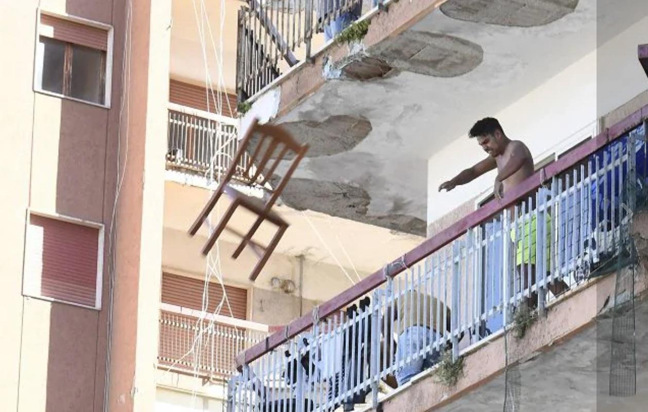 Un bulgaro che da un balcone del Palazzo ex Cirio di Mondragone lancia una sedia durante le proteste per il focolaio Covid (foto Ansa)