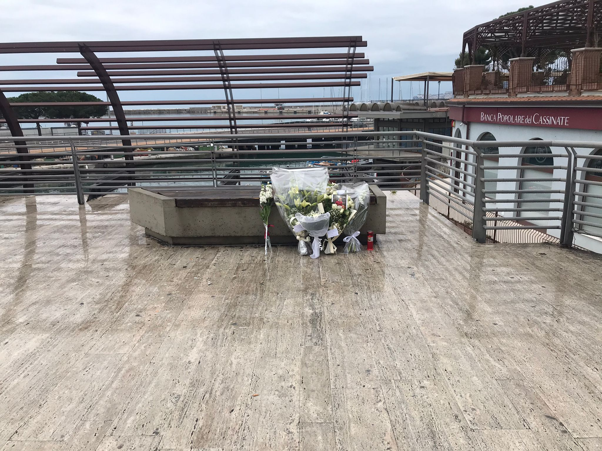 I mazzI di fiori poggiatI nel punto in cui è stato ferito a morte Romeo Bondanesi